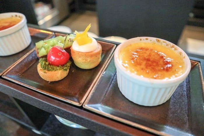 1段目のキウイのタルト、さくらんぼとピスタチオのプチシュー、マンゴーのマフィン、オレンジのクリームブリュレ
